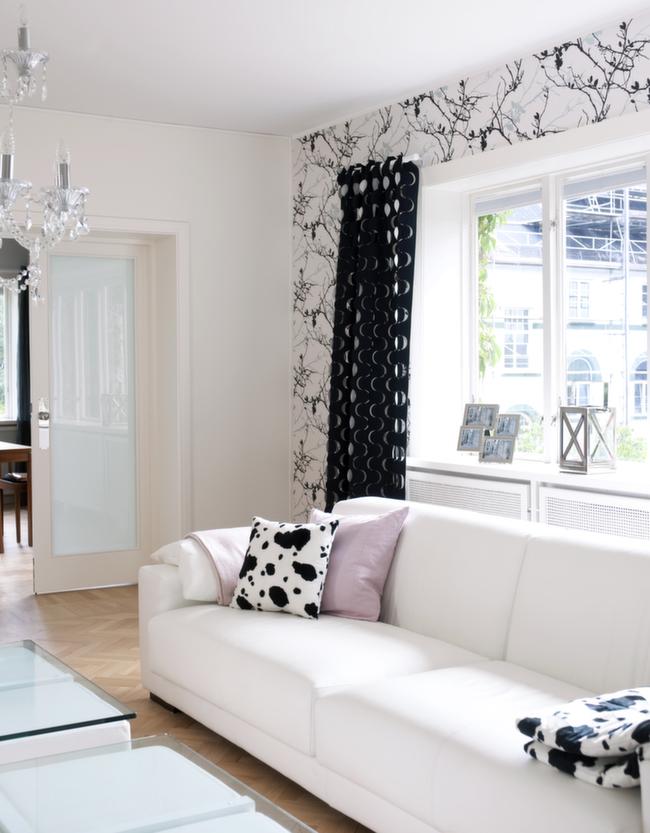 Sort og hvitt, matt og blankt, maling og tapet - kontrastene er mange, men farge- og materialbruken konsekvent.
