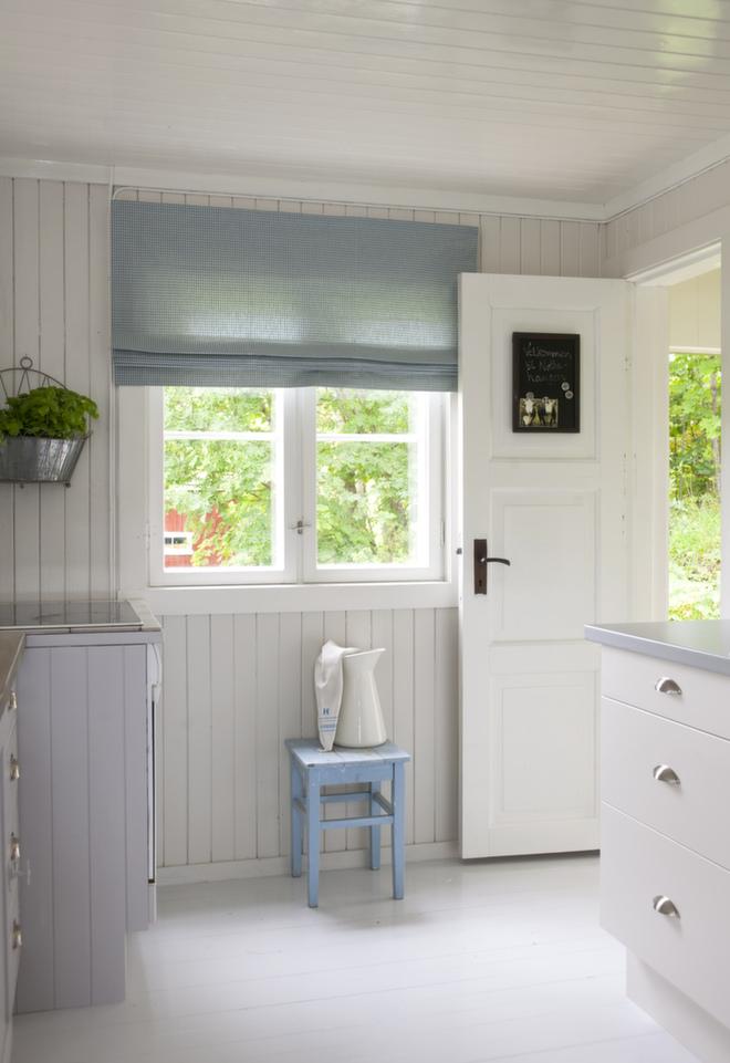 Rett inn på kjøkkenet: Kjøkkenet ligger nå i åpen løsning med stue/spisestue. Hvitmalte tak og vinduer, lys beige vegger og dører samt lysegrått gulv gir et friskt og delikat inntrykk. Liftgardinen er i rutet lin. Innredningen er fra IKEA.