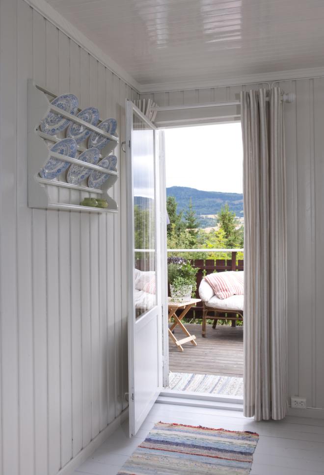 Nyt utsikten: Hytta har en herlig terrasse mot utsikten og kulturlandskapet. De blåmønstrete tallerkenene tar opp de blå detaljene fra kjøkkenet. Det var på denne veggen TV-en sto før, men den ble kastet ut for godt.