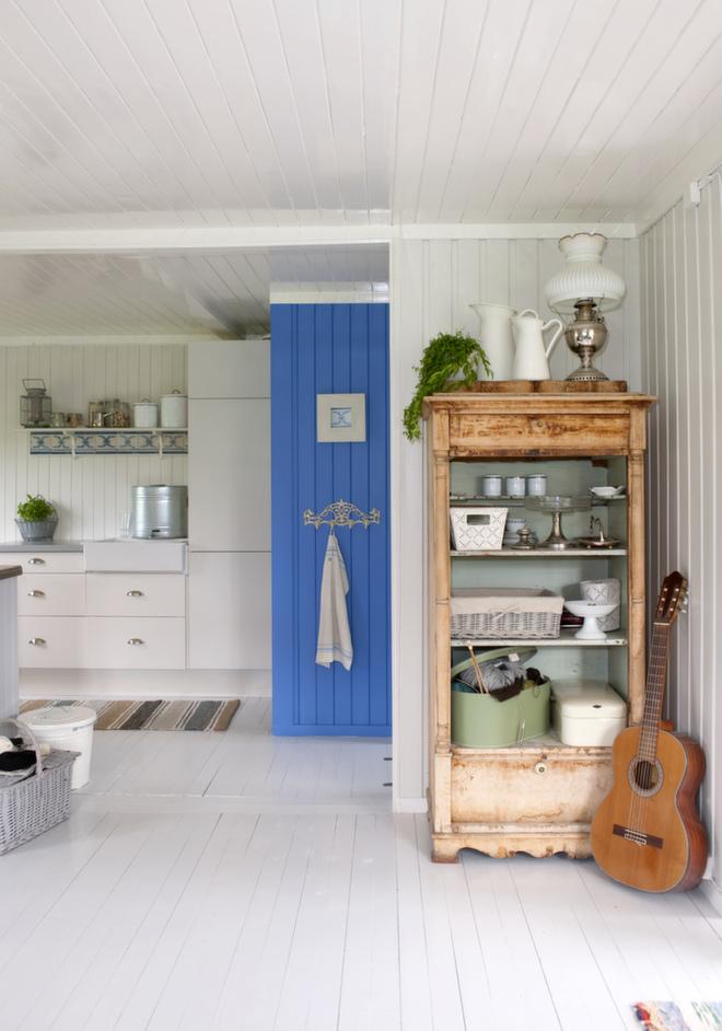 Blått blikkfang: Den blåmalte halvveggen (farge S 3040-R80B) gjør rommet litt rampete, ifølge interiørkonsulent Ellen. Veggen har også en flott stoppeffekt, og fargen ble valgt ut ifra de antikke flisene som er montert under hyllen ved oppvaskbenken. Den gamle pidestallen var fra gammelt av malt innvendig og er et dekorativt og praktisk kjøkkenskap.