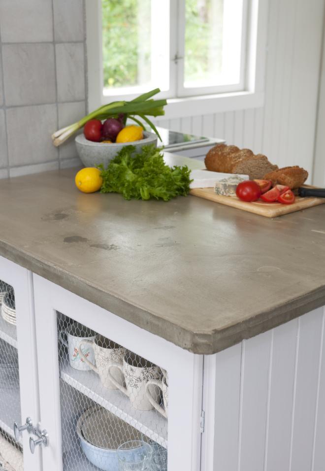 Armert for matlaging: For å skape et litt røffere preg på kjøkkenet, ønsket Mari en plate i betong på kjøkkenøya. Hun fikk sin lokale snekker til å lage en tilpasset ramme, og så fikk mureren i oppdrag å støpe platen. Den er laget i en støpemasse tilsvarende den man bruker i badegulv etc. Denne typen er lettere enn vanlig betong, men veldig sterk. Benkeplaten er armert, og mureren pusset bort porene på toppen. Til slutt ble den lakkert med to strøk gulvlakk.