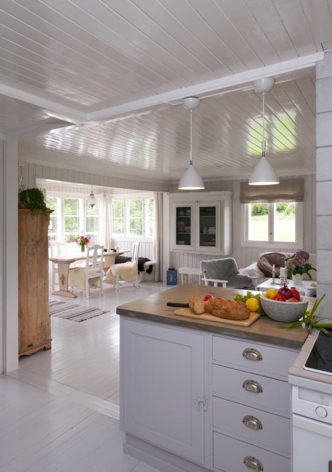 Vekk med platene: Her ser vi hvor lyst og lekkert det er med blankmalt, hvitt tak (90-glans). Takplatene som var i den ene delen av stuen ble fjernet, og nytt tak i samme høyde og panel som resten ga ytterligere lys og luft i rommet. Fra kjøkkensiden har øya lukket skapfront og skuffer. Den er malt i en lys, grålilla nyanse (2502-Y17R). Liftgardinene er i naturlin, og gulvet er malt lysegrått (1502-Y).