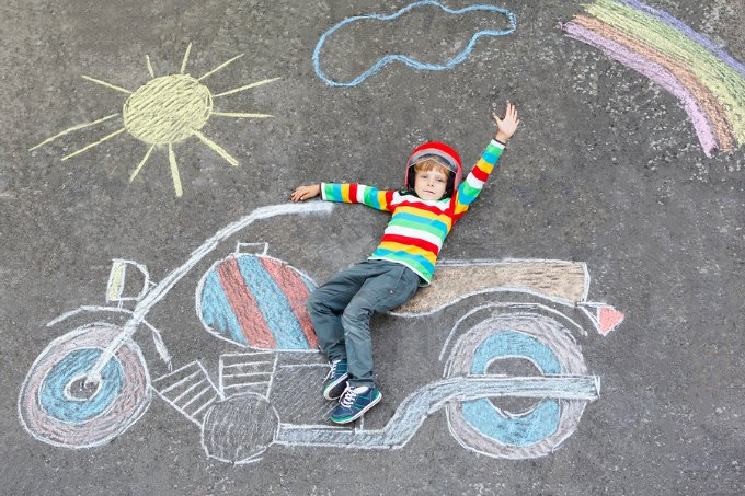 Creative leisure for children: Adorable little child of four years in helmet having fun with motorcycle picture drawing with colorful chalks. Children lifestyle fun concept.