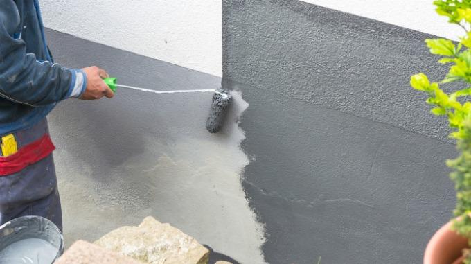 En person maler en vegg grå med malerull.
