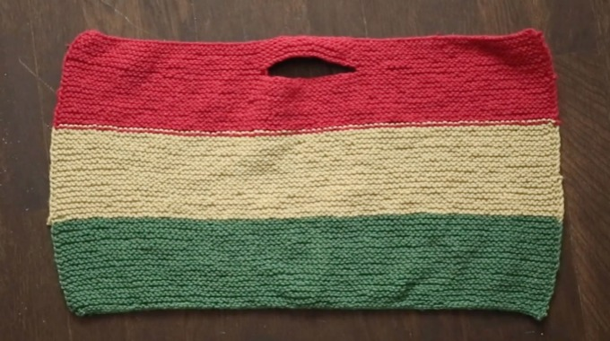 Et strikket håndtak til sitteunderlag i rød, gul og grønn farge.